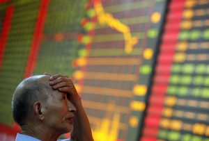 A stock investor reacts near a board displaying stock prices at a brokerage house in Huaibei in central China's Anhui province Monday June 24, 2013. Global stock markets reeled Monday, with Shanghai's index enduring its biggest loss in four years, after China allowed commercial lending rates to soar in a move analysts said was aimed at curbing a booming underground lending industry. (AP Photo) CHINA OUT