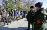 Pro-Russian rebels guard captives, Ukrainian servicemen, prior to their exchange in the small Ukrainian town of Schastya, Lugansk region on October 29, 2015. Ukrainian armed forces and pro-Russian insurgents on Thursday exchanged 20 prisoners in a goodwill gesture designed to get peace talks in the 18-month crisis back on track. The swap took weeks to organise and was the first of its kind since September 8. The pro-Russian eastern militia handed over eight Ukrainian soldiers and one civilian in neutral territory in the predominantly separatist Lugansk province under the watchful eye of observers from the  Red Cross. AFP PHOTO / ALEKSEY FILIPPOV